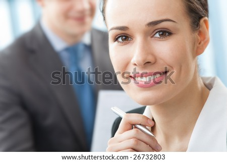 Portrait of successful businesswoman and colleague on background, at office - stock photo