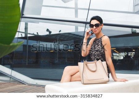 Portrait of successful businesswoman dressed in elegant clothes having mobile phone conversation while sitting near modern building in summer day, smiling female talking on her cellphone outdoors - stock photo