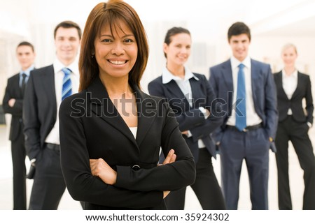 Portrait of successful businesswoman looking at camera with her workteam at background - stock photo