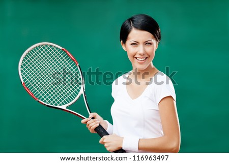 Portrait of successful female tennis player with racquet at the tennis court - stock photo