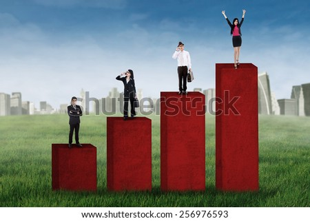 Portrait of successful four businesspeople standing over chart, shot outdoors - stock photo
