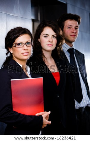 Portrait of successful happy business team posing at office lobby in front of elevator. Dark background. - stock photo