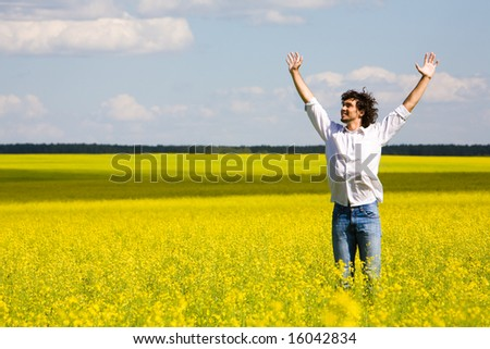 Portrait of successful man in shirt and jeans lifting up hands - stock photo