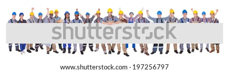 Portrait of successful manual workers with blank billboard against white background - stock photo