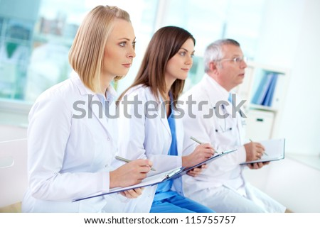 Portrait of successful medical workers listening to the lecture and making notes - stock photo