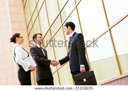 Portrait of successful partners handshaking after making agreement with elegant secretary near by - stock photo