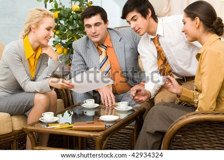 Portrait of successful people communicating in office around table and having tea - stock photo