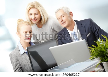 Portrait of successful sales team sitting at office in front of laptop and analyzing financial data. Business people working on new business plan.  - stock photo