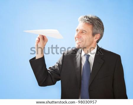 Portrait of successful senior businessman launching a paper plane - stock photo