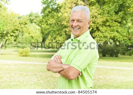 Portrait of successful senior man looking at camera outdoors. - stock photo