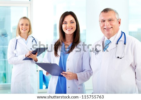 Portrait of successful therapeutists looking at camera in hospital - stock photo