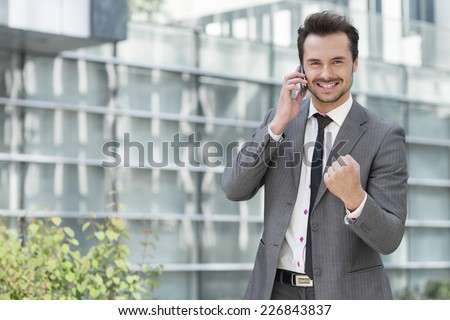 Portrait of successful young businessman using cell phone against office building - stock photo