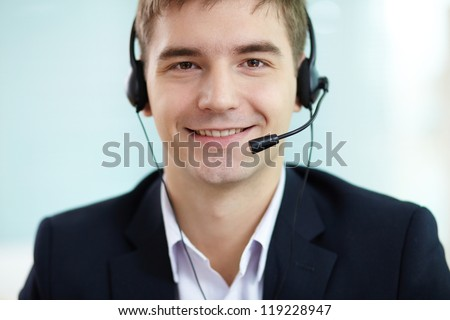 Portrait of successful young man in headset looking at camera - stock photo
