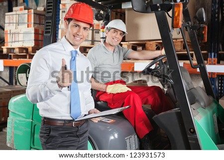 Portrait of supervisor gesturing thumbs up with forklift driver sitting behind - stock photo