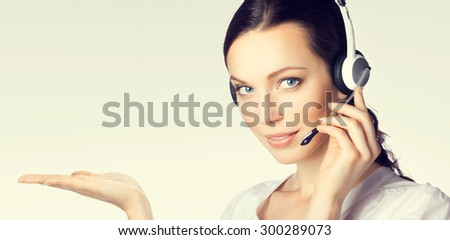 Portrait of support phone operator in headset showing something or blank copyspace area for text or slogan - stock photo