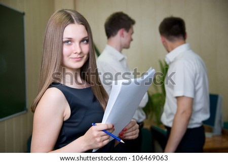 Portrait of sure young girl smiling with colleagues, discussing in a background - stock photo