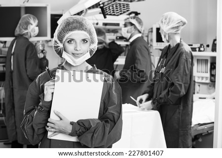 Portrait of surgeons in surgery with doctors working on background - stock photo