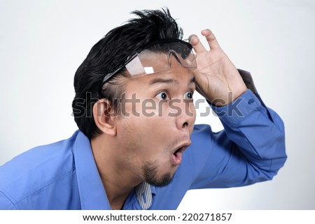 Portrait of surprised asian man in casual shirt keeping mouth open - stock photo