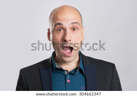 portrait of surprised bald man over gray background - stock photo