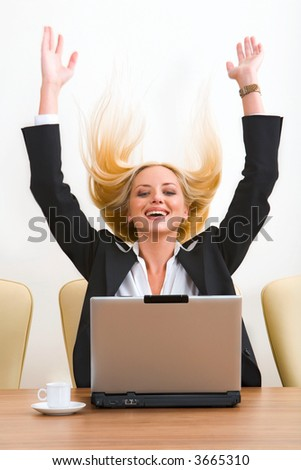 Portrait of surprised blond businesswoman with raised hands sitting at the table with the opened laptop and a cup on it - stock photo