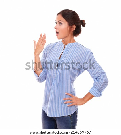 Portrait of surprised charming woman on blue blouse looking to her right while standing on isolated studio - stock photo