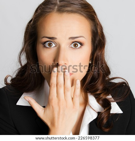 Portrait of surprised excited young business woman covering with hands her mouth, against grey background - stock photo