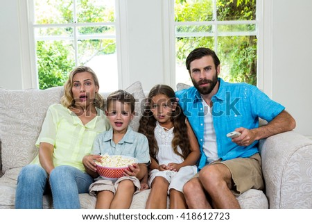 Portrait of surprised family laughing while watching tv at home - stock photo