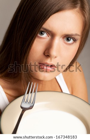 Portrait of surprised girl with plate of milk and fork - stock photo