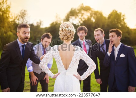 Portrait of surprised groomsmen looking at beautiful bride outside - stock photo