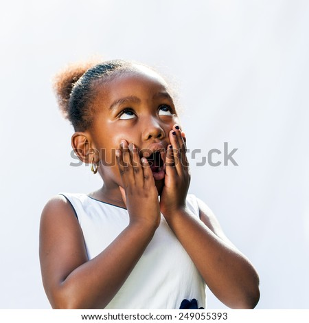 Portrait of surprised little African girl with hands on face looking up.Isolated against light background. - stock photo