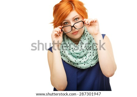 Portrait of surprised red-haired young woman holding glasses on her nose isolated on white background - stock photo