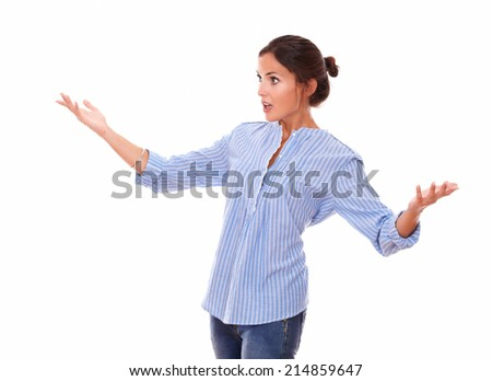 Portrait of surprised woman on blue blouse holding up her hands while looking to her right and standing on isolated white background - copyspace - stock photo