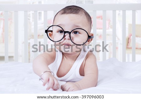 Portrait of sweet baby boy looking at the camera while lying on bedroom and wearing glasses - stock photo