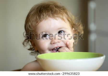 Portrait of sweet little laughing baby boy with blonde curly hair and round cheecks eating from green plate holding spoon and lick fingers closeup, horizontal picture - stock photo