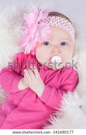 Portrait of sweet three months old baby girl in pink hairband with flower on a fluffy blanket in basket - stock photo