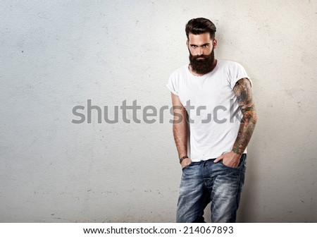 Portrait of tattooed bearded man wearing blank t-shirt - stock photo