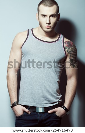 Portrait of tattooed brutal young man with short hair and bristle on face wearing sleeveless shirt, blue jeans and posing over gray background. Hipster style. Studio shot - stock photo