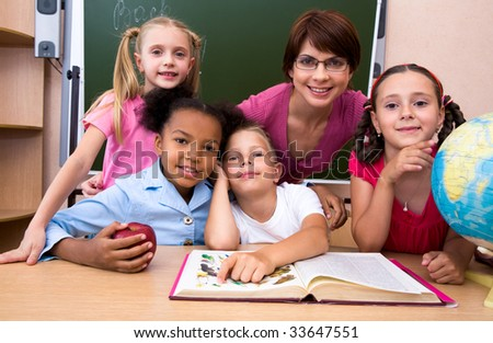 Portrait of teacher and children looking at camera in the classroom - stock photo
