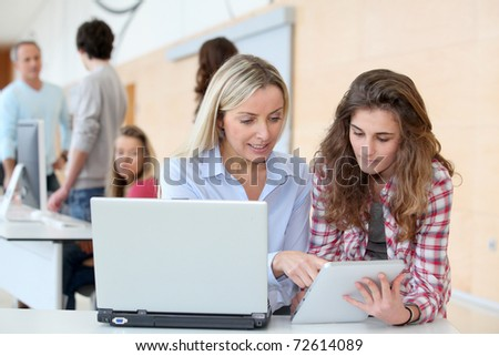 Portrait of teacher and teenage girl in computing class - stock photo