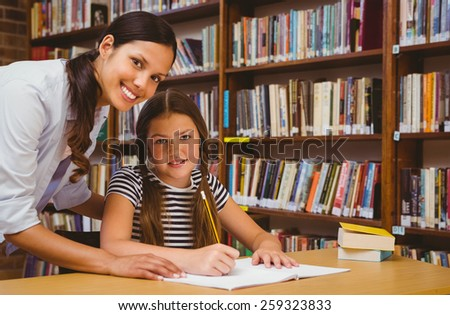 Portrait of teacher assisting little girl with homework in the library - stock photo