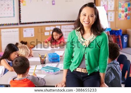 Portrait of teacher in classroom with elementary school kids - stock photo