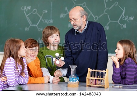 Portrait of teacher instructing students learning molecules - stock photo