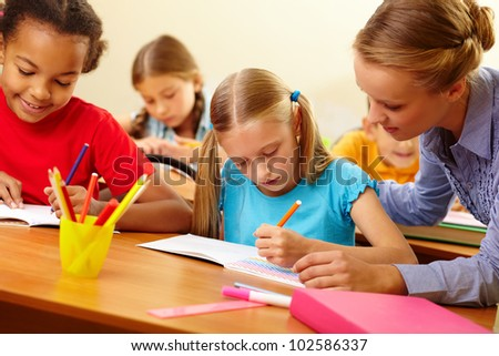 Portrait of teacher looking at a drawing schoolgirl�¢??s copybook at lesson - stock photo