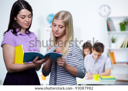 Portrait of teacher looking at her student copybook while explaining mistakes - stock photo