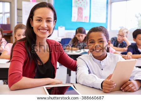 Portrait of teacher with elementary school boy at his desk - stock photo
