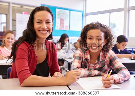 Portrait of teacher with elementary school girl at her desk - stock photo