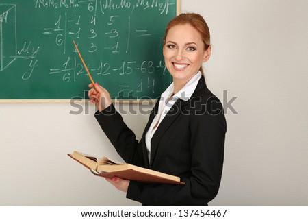Portrait of teacher woman near the chalkboard in classroom - stock photo