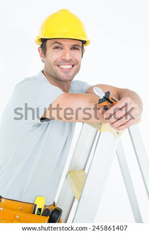 Portrait of technician holding pliers while leaning on step ladder over white background - stock photo