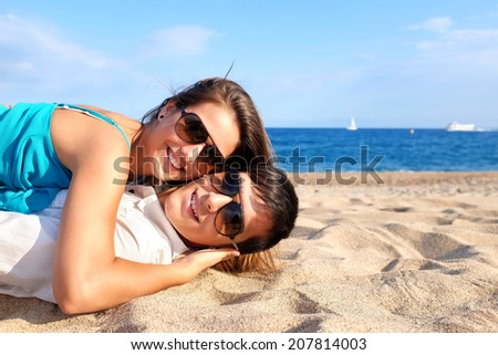 Portrait of teen Couple laying together on beach. - stock photo