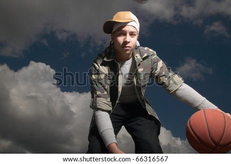 Portrait of teenage boy dribbling basketball - stock photo